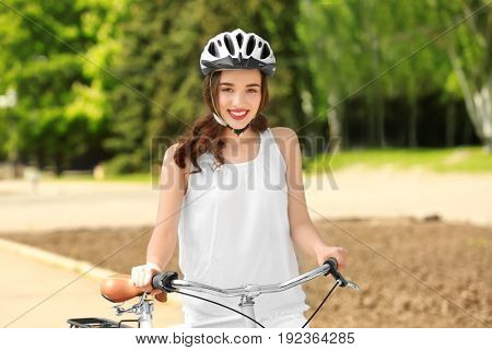 Beautiful young woman with bicycle and helmet in park on sunny day