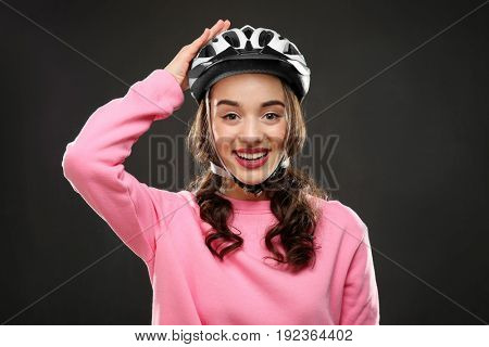 Beautiful young bicycle rider with helmet on dark background