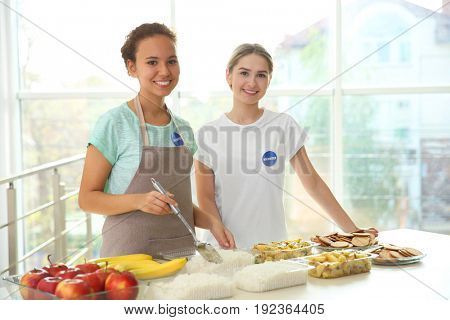 Young volunteers near table with different products indoors