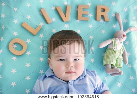 Cute baby lying on bed with word OLIVER composed of wooden letters. Choosing name concept