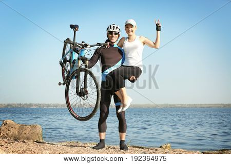 Sporty cyclist holding bicycle and young woman while standing near river