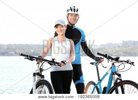 Sporty cyclists with bicycles near river