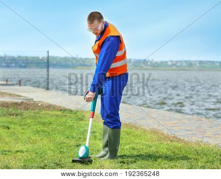 Young worker mowing lawn with grass trimmer outdoors on sunny day
