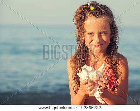 Child with shell. Summer vacation. Girl on sea background