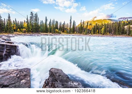 The full-water bubbling waterfall of Athabasca. Clear autumn evening in Canada. Cold blue water at sunset. The concept of extreme and ecological tourism