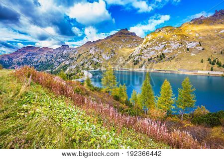 The concept of ecological and extreme tourism. Mountain Lake Lago di Fedaia, Dolomites. Glacial lake with clear cold water