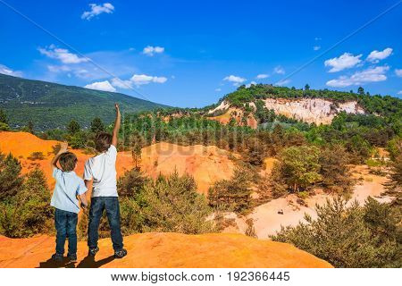 Orange and red picturesque hills. Languedoc - Roussillon, Provence, France. Two boys of seven and four years admire the magnificent nature