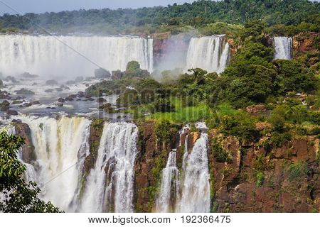 Powerful two-stage waterfall creates a watery dust and a rainbow. Several waterfalls from Iguazu Falls. The concept of exotic and extreme tourism