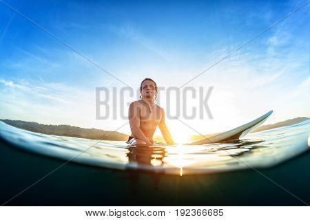 Young man sits on the surfboard in the ocean and waits wave during his sunrise surf session