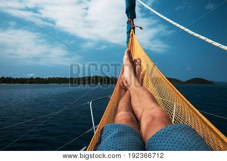Man relaxes in a hammock set on a yacht