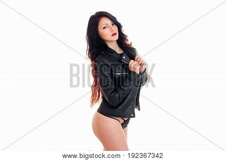 Cute brunette woman in black leather jacket and panties looking at the camera isolated on white background