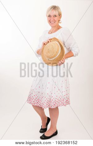 portrait of a attractive blond haired mid aged european woman wearing white dress showin happy face holding summer had - full body - studio shot on white background.