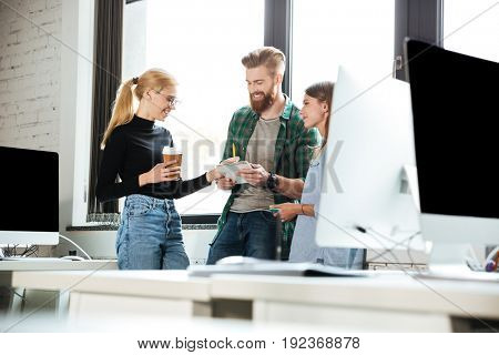 Image of young concentrated colleagues in office talking with each other. Looking aside.