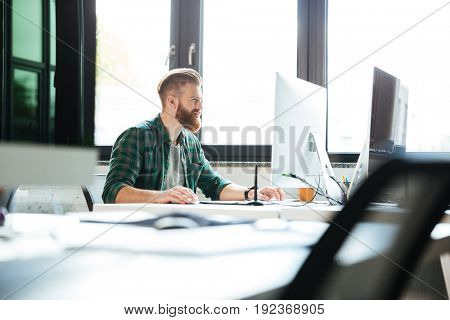 Picture of young handsome man work in office using computer. Looking aside.