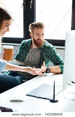 Picture of two young colleagues work in office using computers. Looking aside. Focus on man drinking coffee.