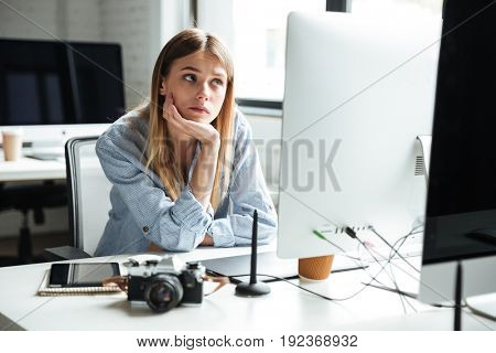 Image of serious young woman work in office using computer. Looking aside.