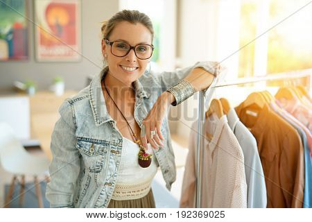 Cheerful clothing salesperson standing in shop