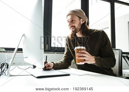 Image of young handsome man in office using computer. Looking aside drinking coffee.