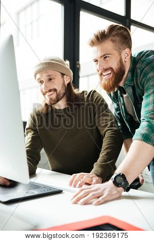Photo of young happy men colleagues in office using computer. Looking aside.