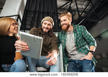 Photo of young smiling colleagues in office using tablet computer. Looking aside.