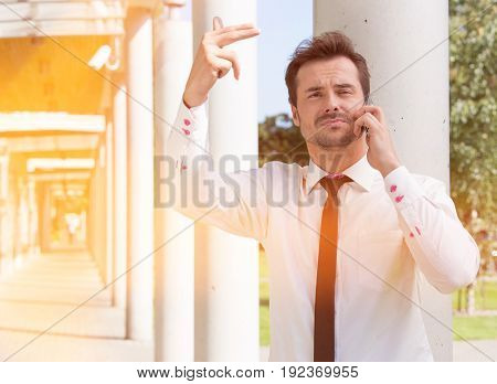 Confident young businessman gesturing while using mobile phone outside office