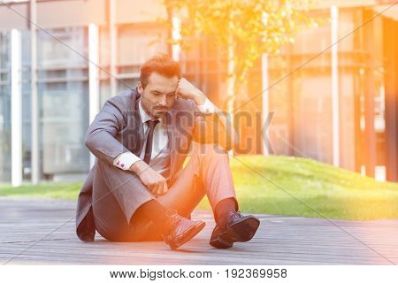 Full length of depressed businessman sitting on path outside office