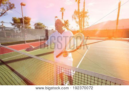 Happy senior male tennis player offering handshake on court