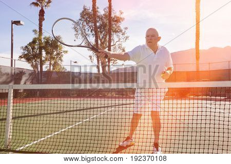 Senior male tennis player preparing to serve on court
