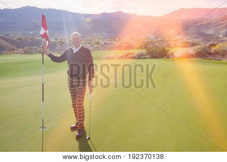 Full length portrait of happy senior male golfer holding flag and putter at golf course