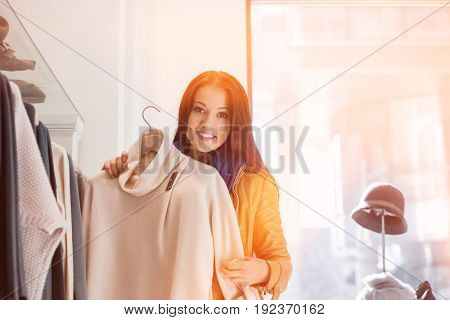 Portrait of young woman choosing sweater in store