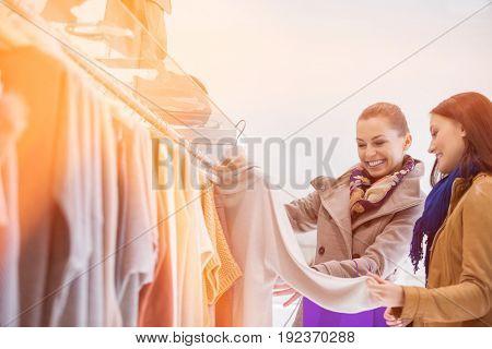 Happy friends choosing sweater in store