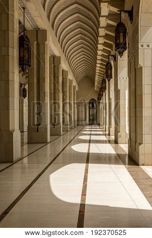 MUSCAT, OMAN - CIRCA AUGUST 2016: IArchitectural View of Arch Colonnade in Courtyard on Sunny Day, Sultan Qaboos Grand Mosque, Muscat, Oman