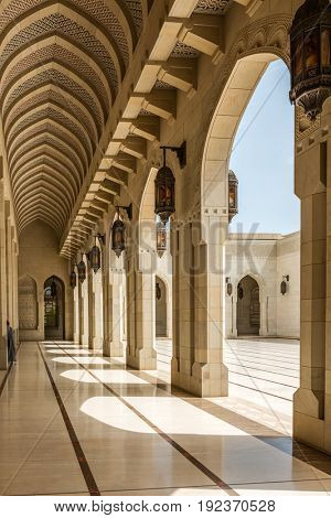 MUSCAT, OMAN - CIRCA AUGUST 2016: IArchitectural View of Courtyard with Arch Colonnades on Sunny Day with Blue Sky at Sultan Qaboos Grand Mosque, Muscat, Oman