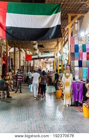 DUBAI, UAE - CIRCA AUGUST 2016:Tourists shopping for souvenirs in an Arab market walking through a covered mall lined with bright merchandise, UAE