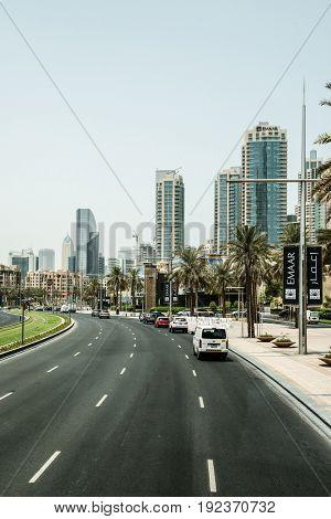 DUBAI, UAE - CIRCA AUGUST 2016:Modern Urban Multi Lane Street Through Downtown Business District with Skyscrapers, Palm Trees and Light Traffic on Sunny Day, Dubai, United Arab Emirates