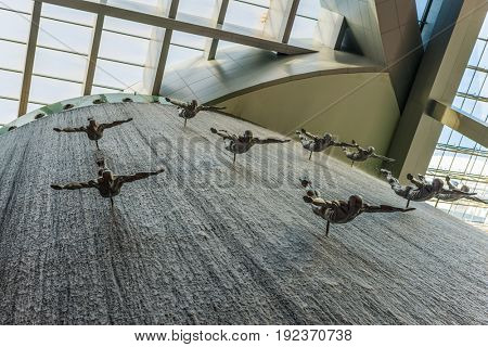 DUBAI, UAE - CIRCA AUGUST 2016: Artificial waterfall with sculptures of flying divers, with glass and steel roof background at Dubai mall interior