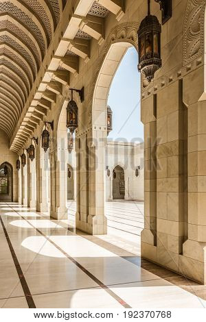 OMAN, MUSCAT - CIRCA AUGUST 2016: Architectural View of Courtyard with Arch Colonnades on Sunny Day with Blue Sky at Sultan Qaboos Grand Mosque, Muscat, Oman