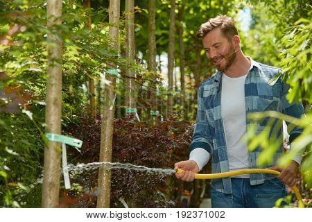Horizontal outdoors shot of male professional gardener standing with hose and watering plants in the garden.