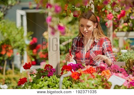 Horizontal outdoors shot of smiling young woman splashing water and doing horticulture job in the garden.