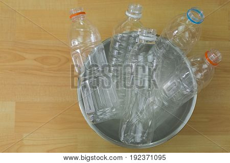 Emptied recyclable clear plastic mineral soda water bottles in a bowl on wooden background with copyspace