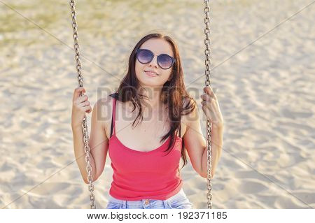 Portrait of young woman swinging at the beach. Happy female tourist with long hair trendy pink top and blue shorts having fun at the beach