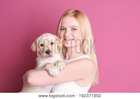 Beautiful young woman with cute labrador retriever puppy on color background