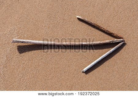 Arrow made up of dry sticks on the sand
