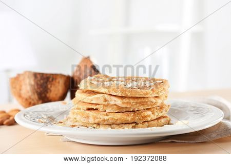 Delicious coconut pancakes decorated with almond shavings on table