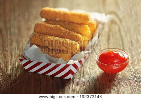 Paper box with cheese sticks on table