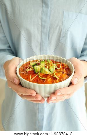 Woman holding bowl with delicious chili turkey, closeup