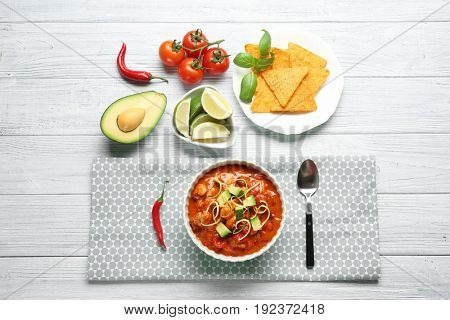 Delicious chili turkey, fresh vegetables and nachos on table