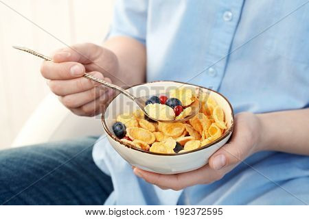 Human hands holding bowl with corn flakes and berries for breakfast