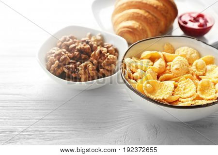 Tasty breakfast with corn flakes in bowl on white table