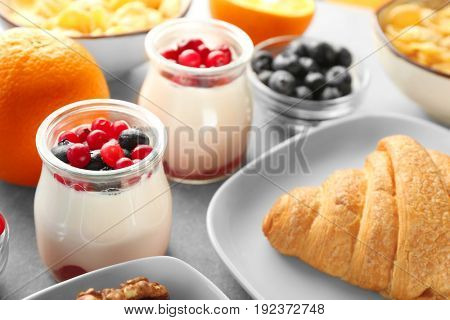 Jar with yogurt and served breakfast on table